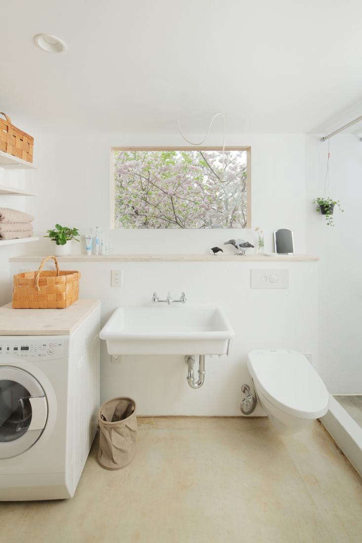 an all white combination bath and laundry room with simple wood shelving in arc 30