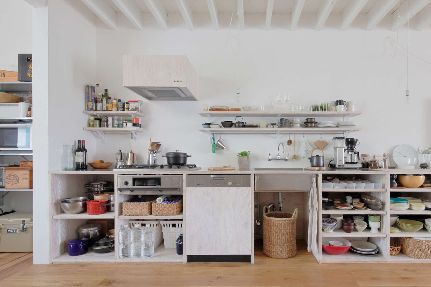 The open kitchen is composed of larch plywood finished with translucent whiteOsmo Wood Wax—a combination also used for the wall storage, vent cover, and Miele dishwasher panel. The counter is stainless steel and under the cooktop is a shallow fish grill.
