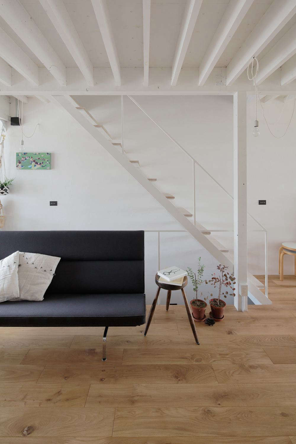The ceiling beams and wooden stair treads play off each other in a rhythmic pattern. &#8