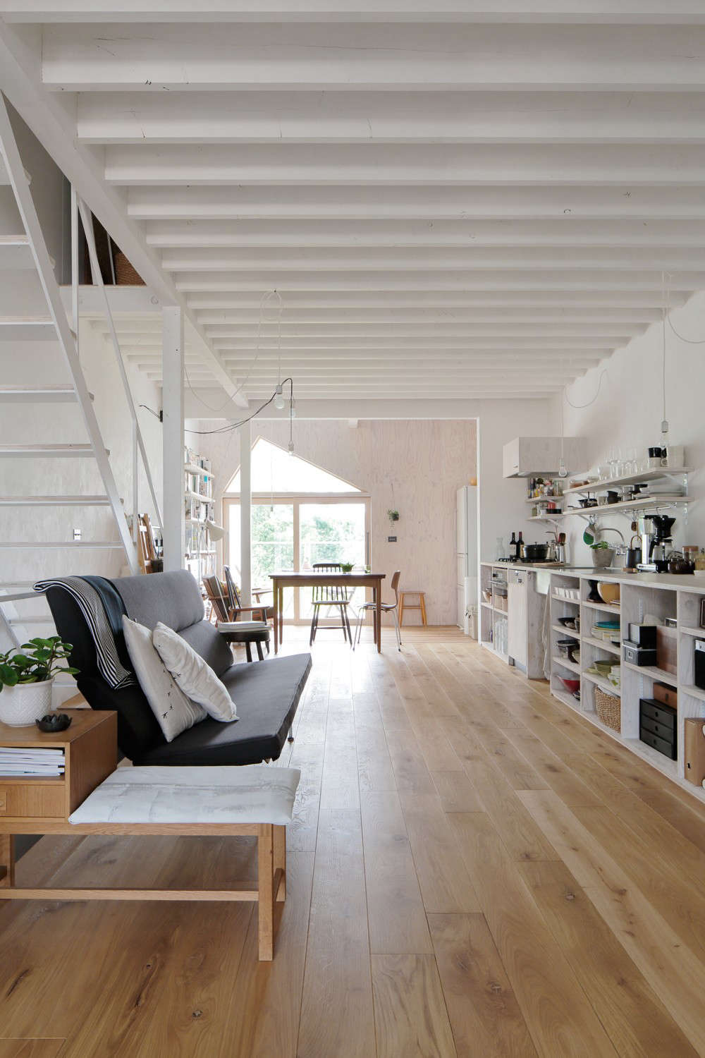 An open kitchen runs along the second floor anchored by living and dining balconies at either end.