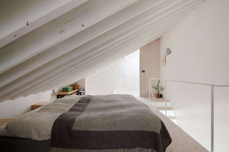 the bed is angled under the eaves next to a sloping side window. building codes 16