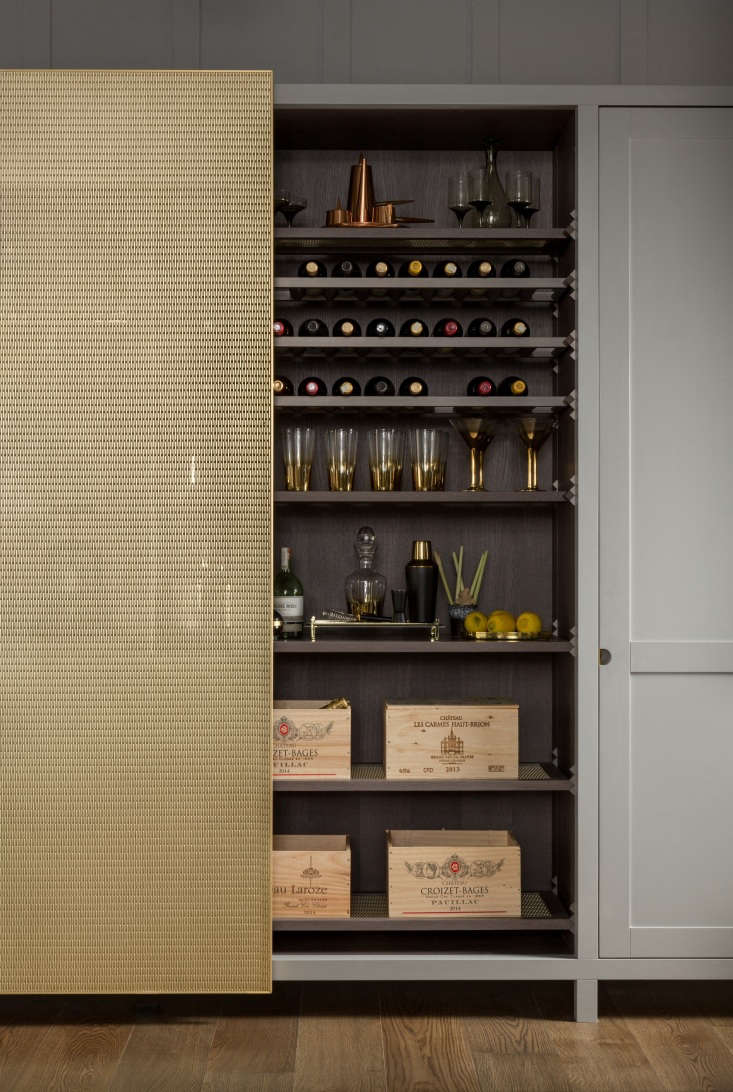 behind the sliding brass mesh door is a wine section detailed with lanserring&a 21