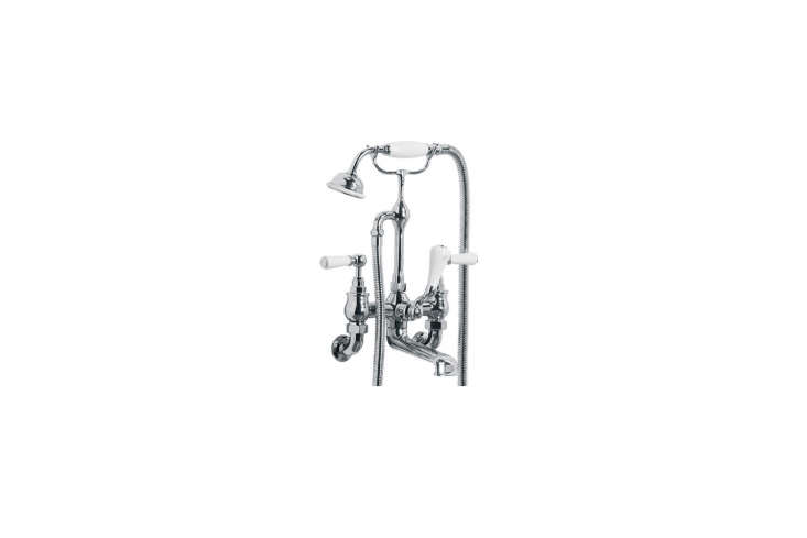 The freestanding bath is equipped with a Lefroy Brooks Classic Wall-Mounted Tub Filler with Handshower; $
