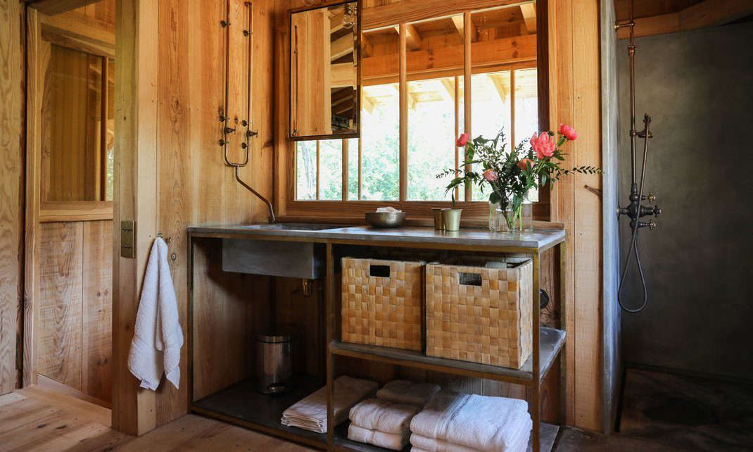 There are three baths; this one has an industrial-style sink unit and exposed piping. (For more faucets like this one, see Trend Alert:  DIY Faucets Made from Plumbing Parts.)