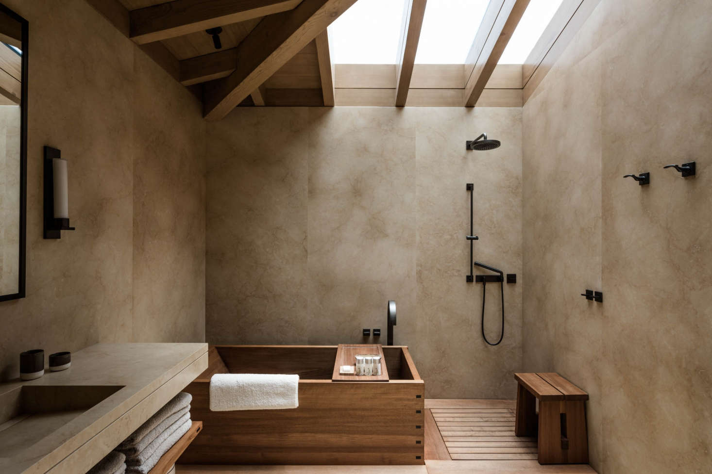 The walls and floors of the bathrooms are wrapped in Jerusalem limestone and the soaking tubs are made of teak; the hardware is bronze and the fixtures are from the Dornbracht MEM Line.