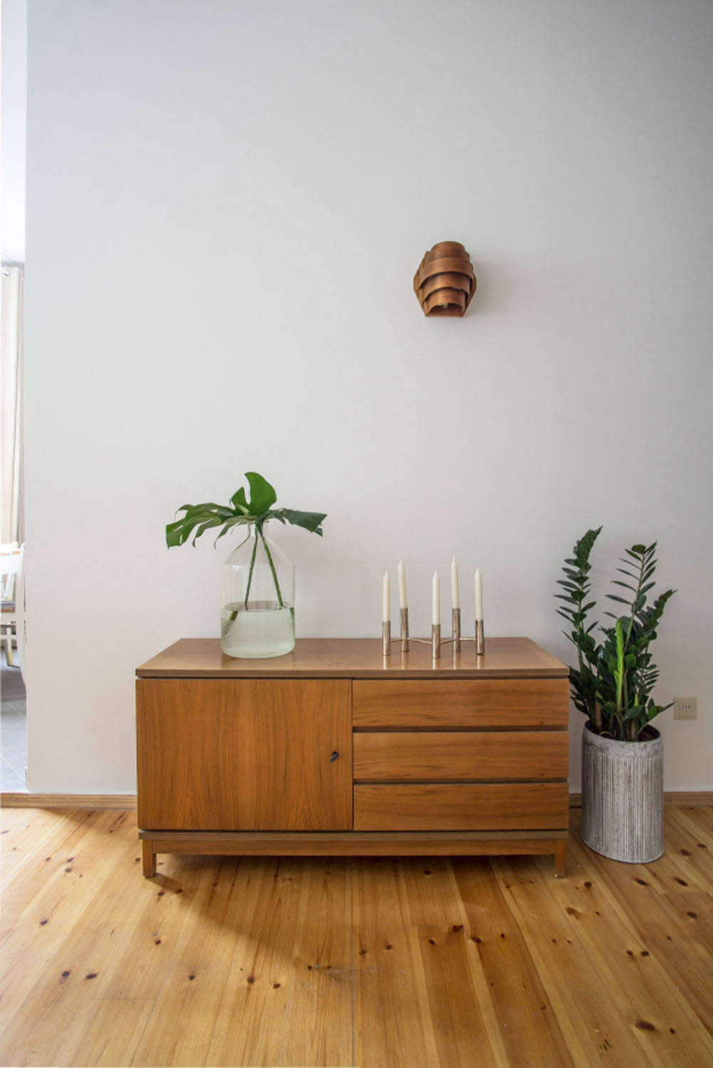 Ninety percent of the furniture is from antiques and vintage stores. Here, a wood wall sconce found in a Kreuzberg shop, a cabinet bought from an online antiques dealer, and a vase and candleholder from the local flea coexist harmoniously.