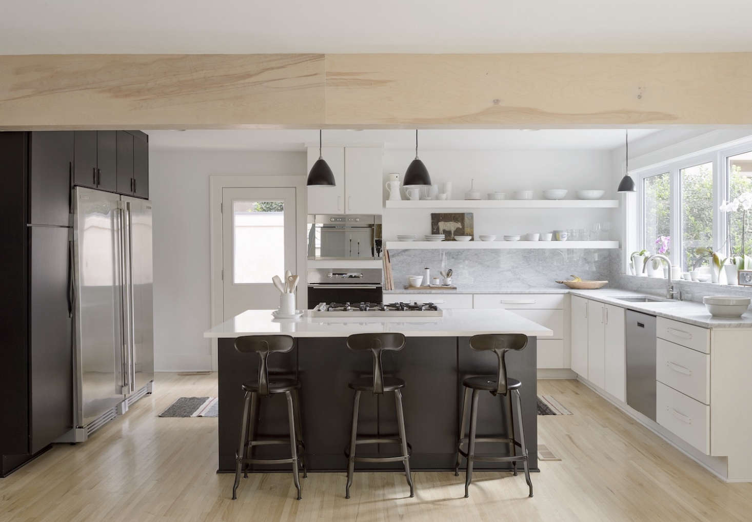 Izabella and Brandon worked with a local kitchen design store on the black and white cabinets; the design was their own. The red oak hardwood floors were bleached three times to achieve the look (for more seeScandi Whitewashed Floors: Before and After). Photograph by Matthew Williams fromBefore & After: Remodelista Contributing Editor Izabella Simmons Shares Her Scandi-Inspired Remodel.