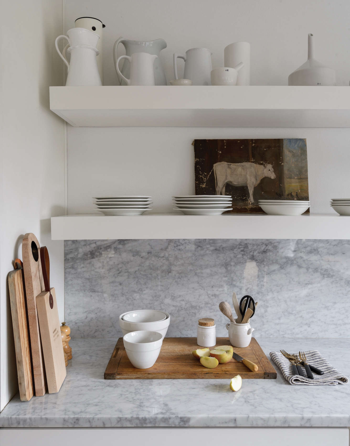 The marble countertop and backsplash are Carrara marble. The open shelves are stocked with a collection of white ceramics and vintage ironstone.Photograph by Matthew Williams fromBefore & After: Remodelista Contributing Editor Izabella Simmons Shares Her Scandi-Inspired Remodel.