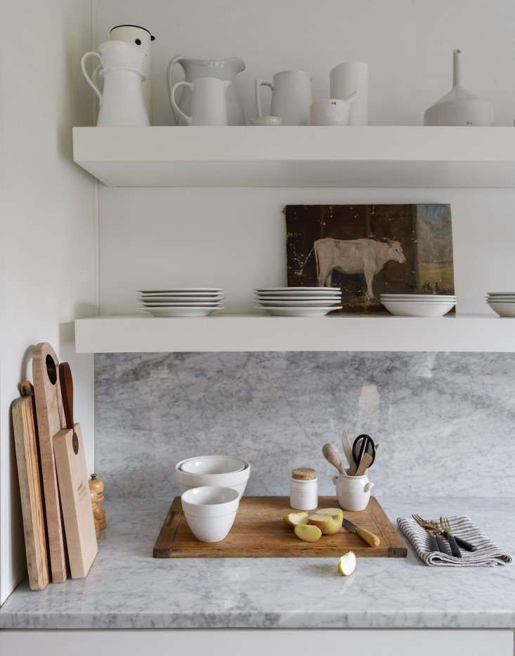 The marble countertop and backsplash are Carrara marble. The open shelves are stocked with a collection of white ceramics and vintage ironstone. Photograph by Matthew Williams from Before & After: Remodelista Contributing Editor Izabella Simmons Shares Her Scandi-Inspired Remodel.