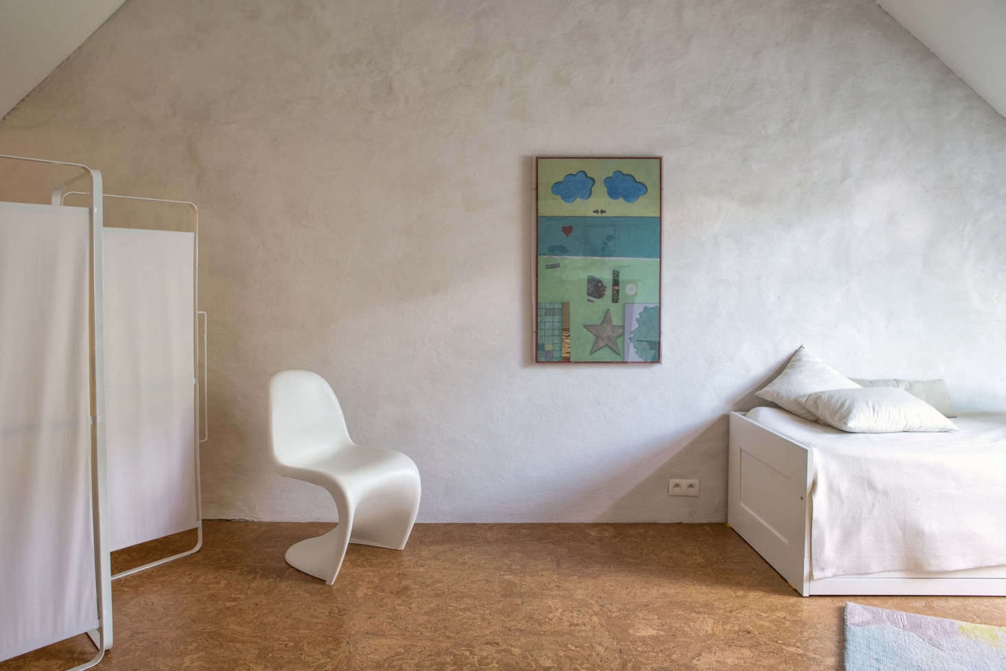 The upstairs loft has two bedrooms and a bathroom with cork flooring and plaster walls. Shown here is the Serax Daysign Folding Screen, a Verner Panton Chair, and an Ikea Brimnes Daybed.