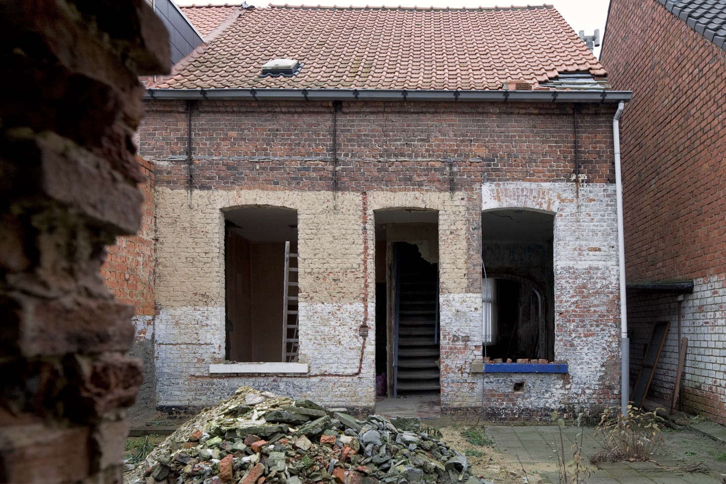 The house exterior during the renovation where the facade and roof were restored, windows and doors were replaced, and two skylights added.
