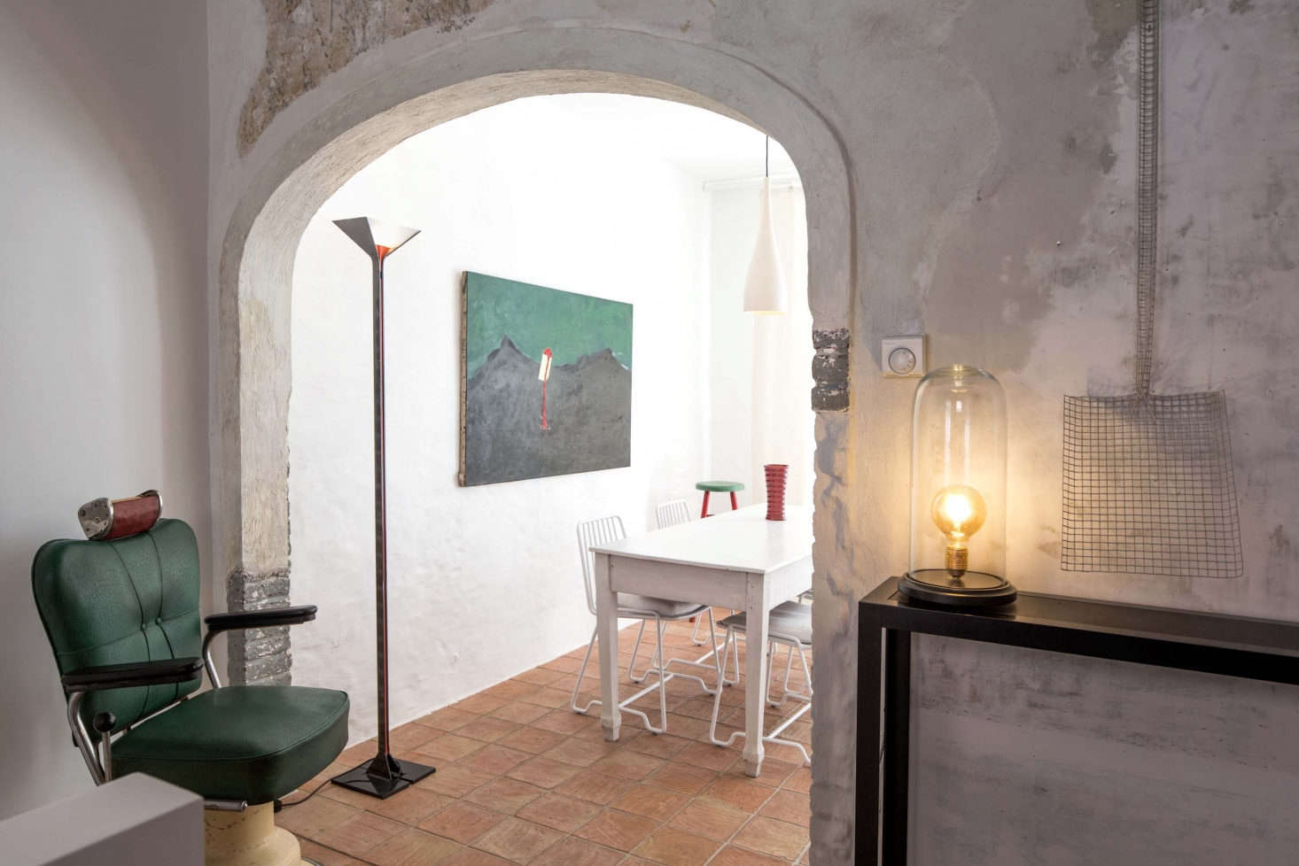 Through the arched doorway is a vintage green leather barber stool, a bell jar table lamp, and Shovel Wire Netting Sculpture by Terry Powell for Serax.