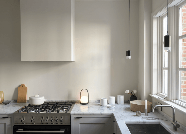 The amber glass vase is Luca Nichetto for Mjölk and the gray glass bowl is Studio Prepa. The range is a Bertazzoni 30-inch duel fuel model (a JIA Inc. Ceramic Steamer sits atop). The light is the Menu Carrie LED Table Lamp and the kitchen window light fixture is the Wireflow LED Pendant by Arik Lévy for Vibia. The faucet is the Vola KVloading=