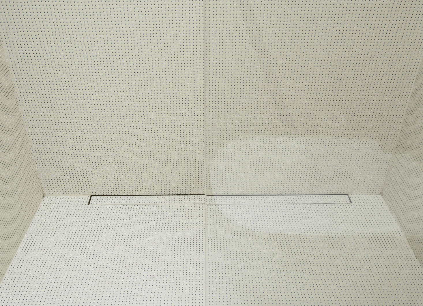 The tiles on the bathroom floor and shower walls are the ceramicPico Tiles by Ronan & Erwan Bouroullec for Mutina in Blue Dots Blanc. The drain is an ordinary linear shower drain with a tile insert.