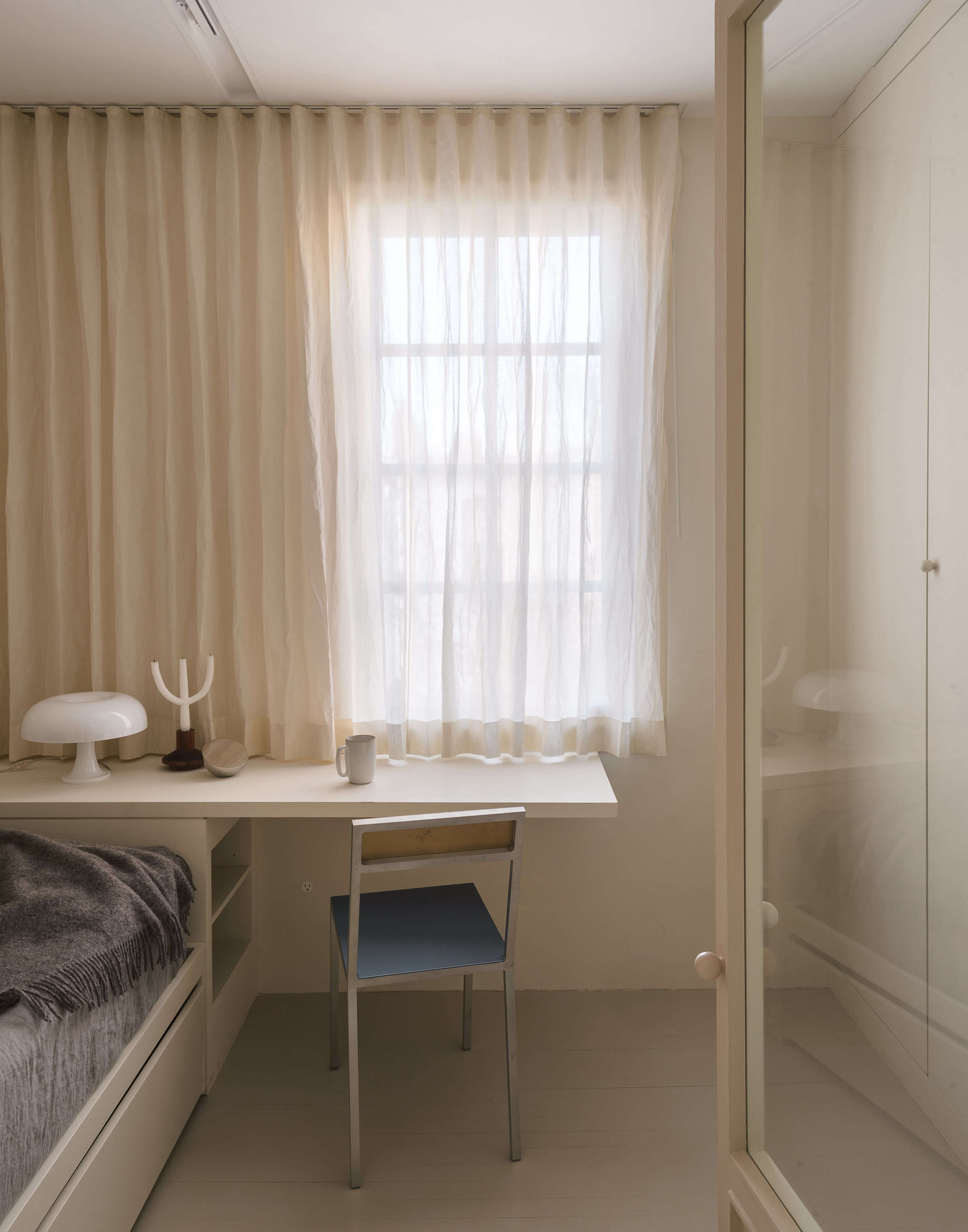 Parked at the custom desk is a steel chair fromBelgian husband-and-wife team Hannes Van Severen and FienMuller.The owner and designers both welcomed the investment of design-as-art, the chair being one of them. The curtains throughout the bedroom areKinnasandComo (a discontinued linen fabric with a metallic weave), that run on a track.Photograph byMatthew Williamsand styling byAlexa HotzfromA Luminous, Euro-Style Row House in Washington, DC, Courtesy of Studio Oink.