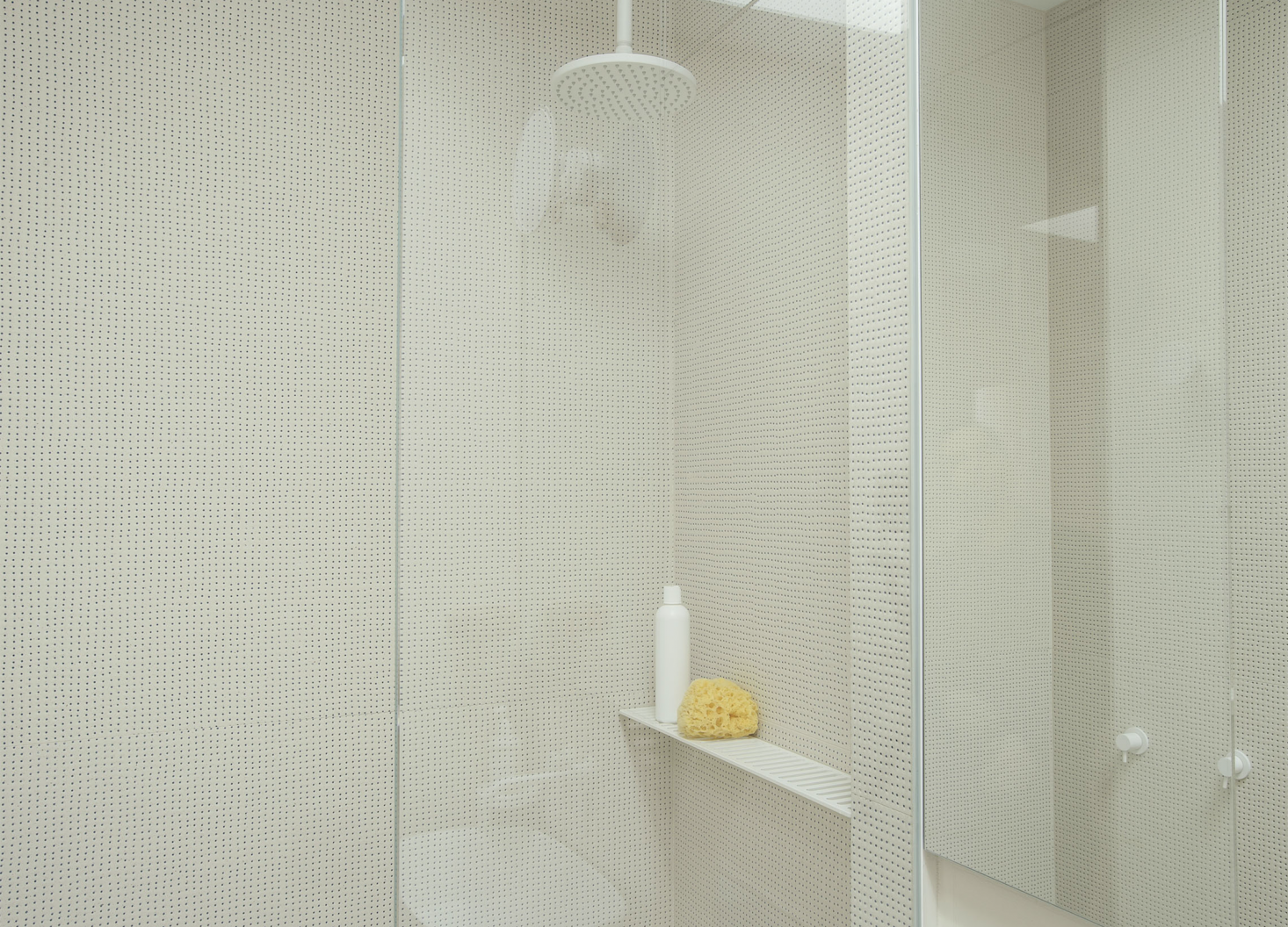 Wall tiles with a pin-size blue dot give the bathroom shower a perforated look. Photograph byMatthew Williamsfor Remodelista; styling byAlexa Hotz.