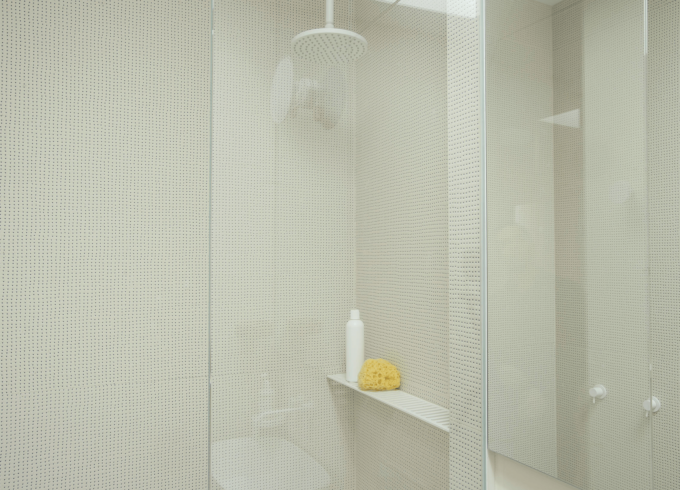 Wall tiles with a pin-size blue dot give the bathroom shower a perforated look. Photograph by Matthew Williams for Remodelista; styling by Alexa Hotz.