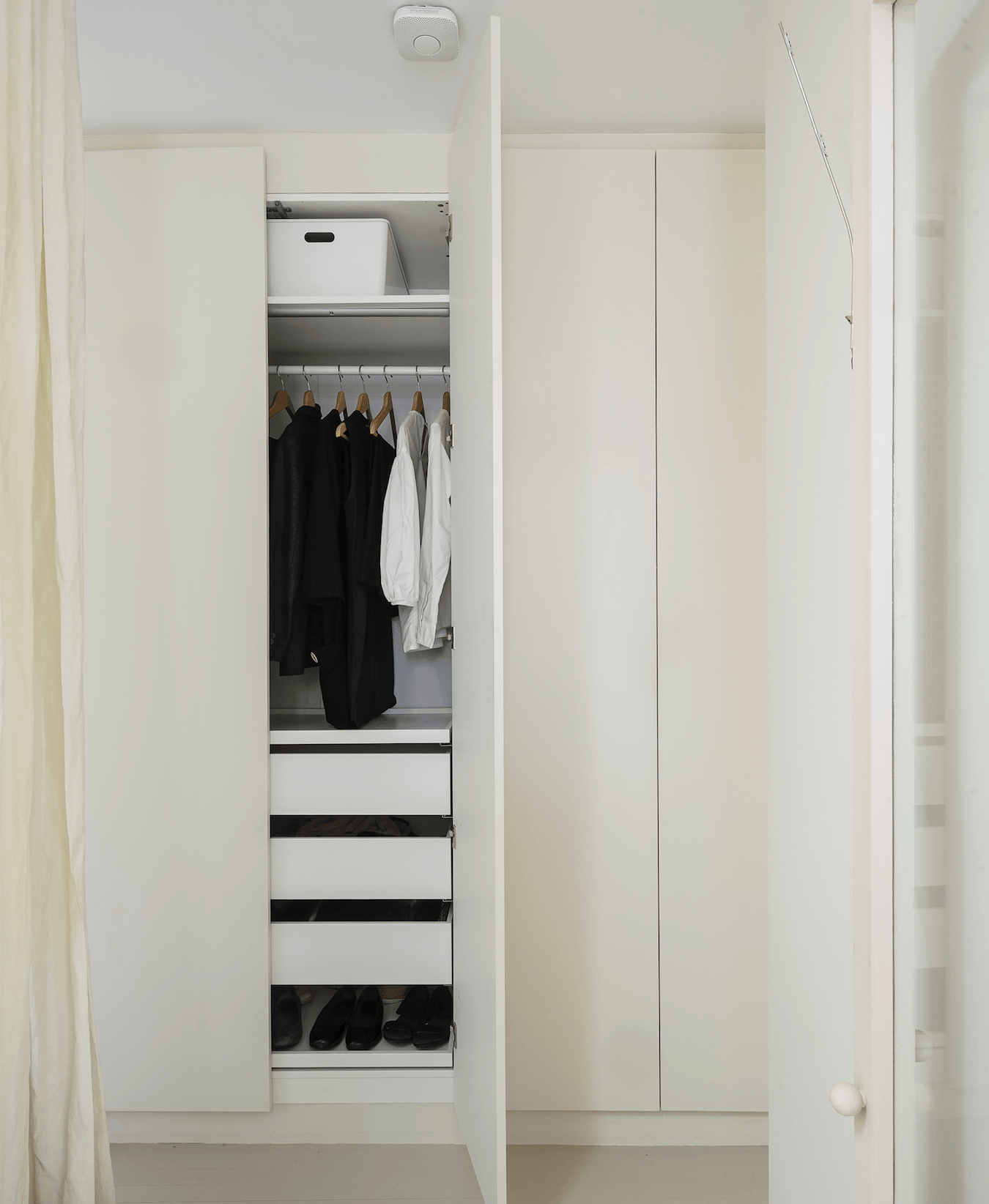 The IkeaPAX Wardrobe Systemserves dual function; it acts as both closet and partition between the hall and the master bedroom. The doors are painted inFarrow & Ball&#8