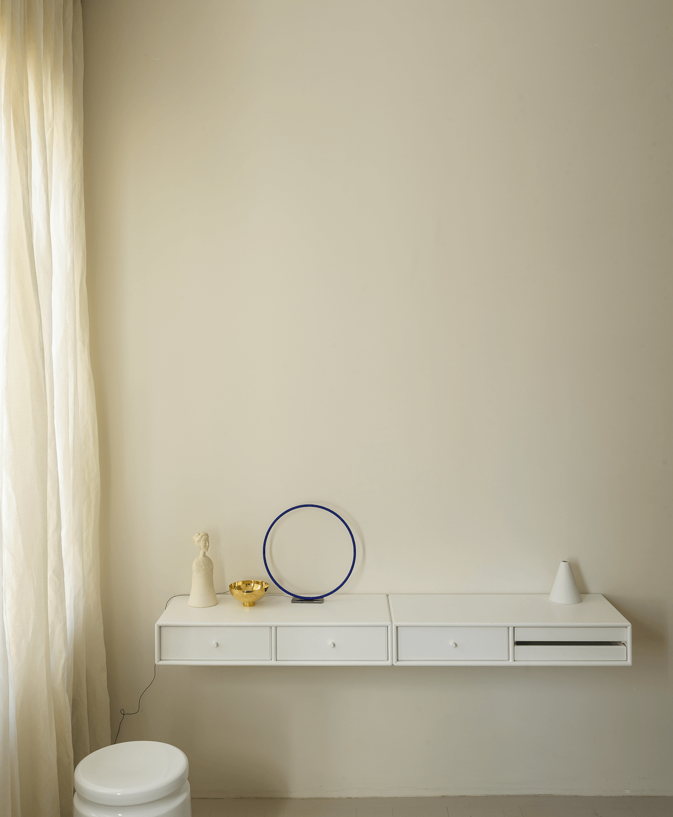 The wall-mounted shelf is the Montana Møbler Write Wall Desk in Snow. Sitting atop: a sculpture byJiro Yoshida, anIlse Bowl by Georg Jensen, aCatellani & Smith Sorry Giotto Table Lamp, and aMarlies Neugebauer Cone Vase. The stool is the Discipline Last Stool by Max Lamb.