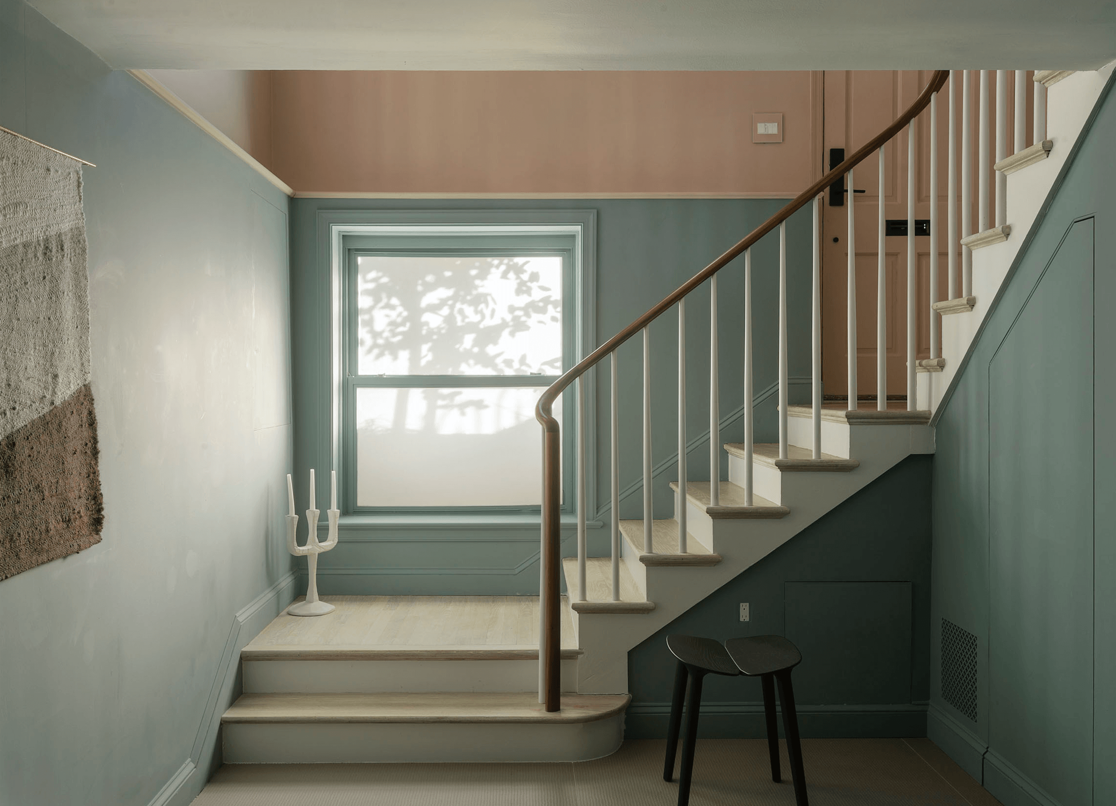 The lower level is paintedOval Room Blue from Farrow & Ball, signaling a change in palette. Studio Oink designed flush storage cabinets under the stairwell. The textile wall hanging is a private commission from Alessandra Taccia for Studio Oink.