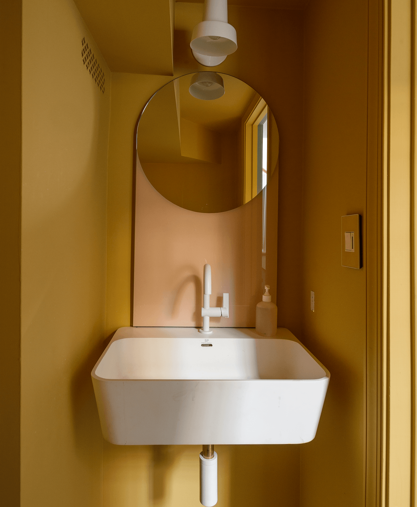 The bath has aHay Shapes Mirror, Porcelanosa Krion Sink (discontinued), matte white Newport Brass Priya Faucet, and Allied Maker Composers Sconce. The flush grille is the Caspian pattern from Majestic Vent Covers.
