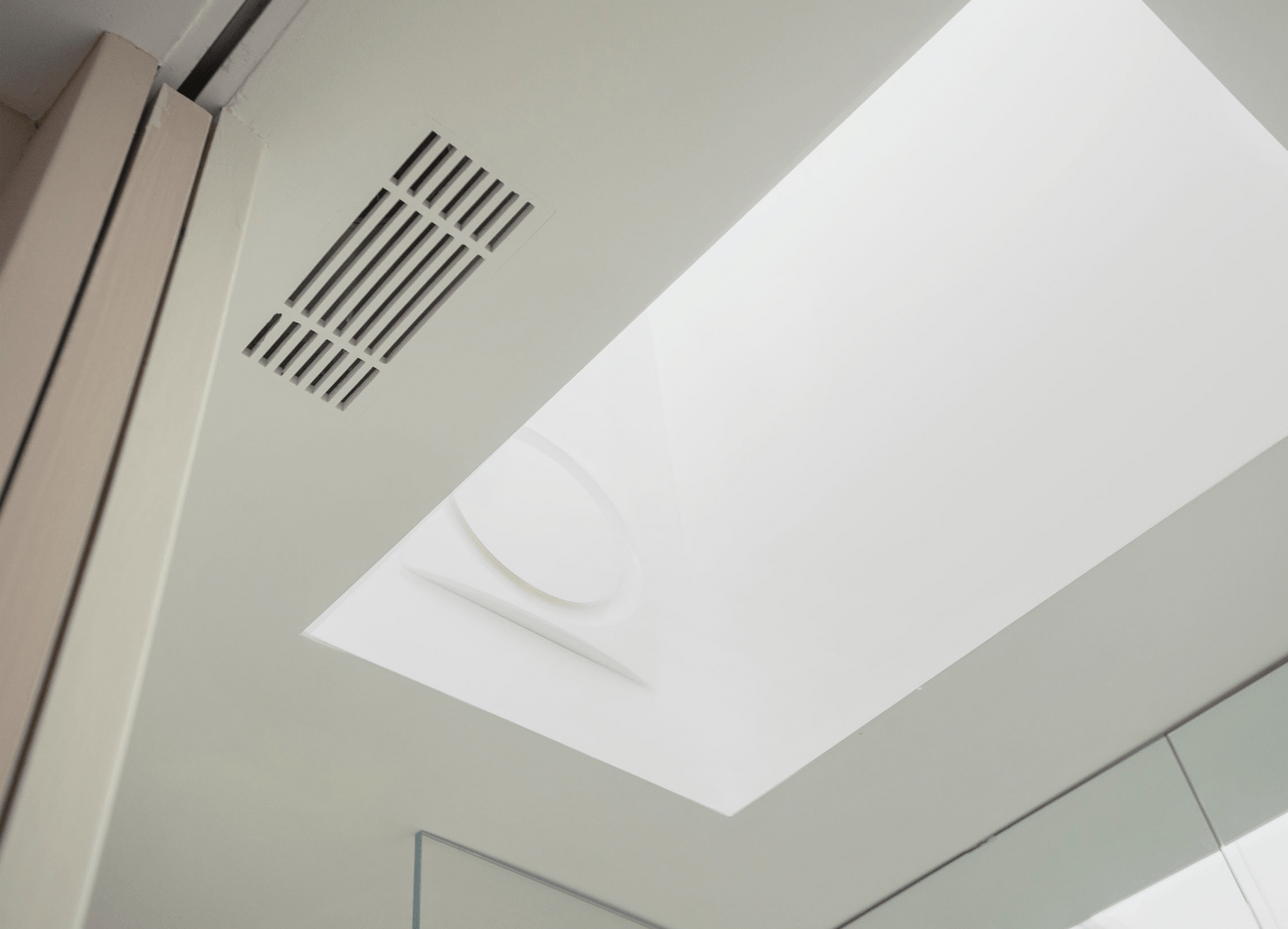 Studio Oink integrated a skylight into the bathroom to bring natural light into the windowless space. Seen here, a frameless vent grille, theLinear Grille ($.60) from Majestic Vent Covers, installed flush.