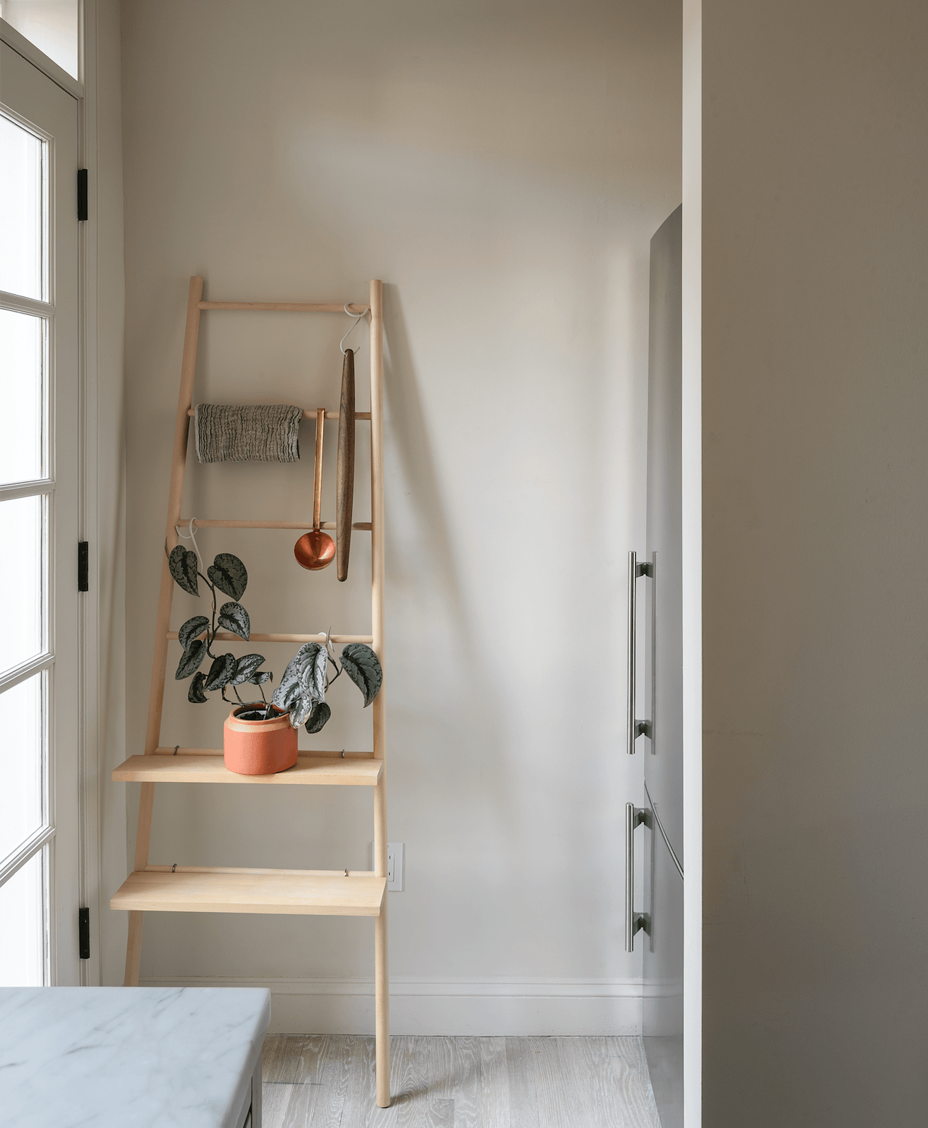 Studio Oink extended the wall to create a nook for the refrigerator, a Liebherr CS00.The owner added a Verso Design Tikas Ladder in birch, with twoTikas Shelves for extra storage.