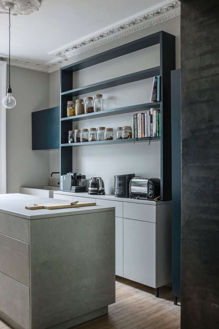 The bookcase-like coffee and tea station is painted a proprietary color. For a similar palette, see Farrow & Ball&#8