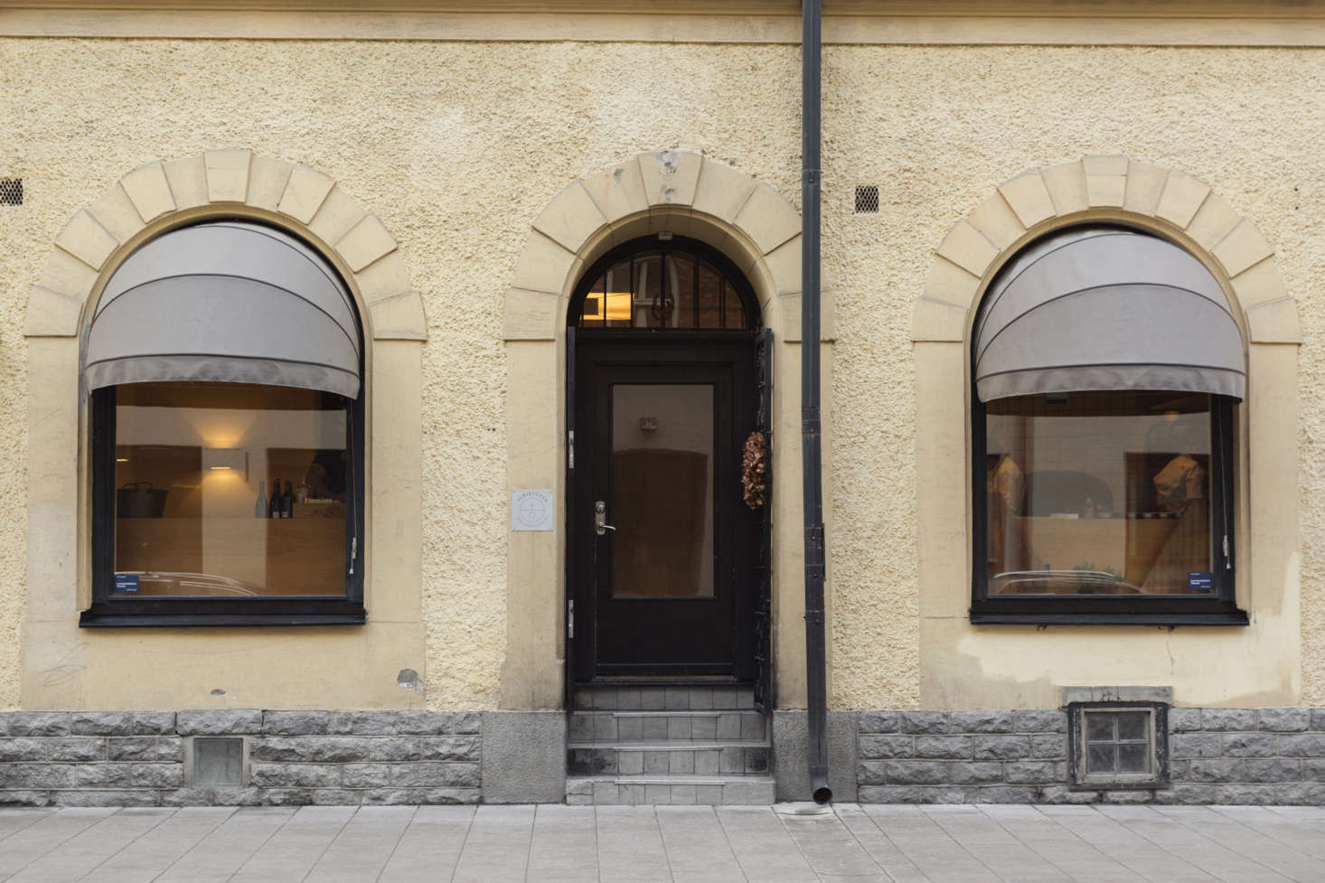 The stately exterior of Agrikultur, with muted tones and awnings. Note also: the dried-flower wreath hanging on the black front door.