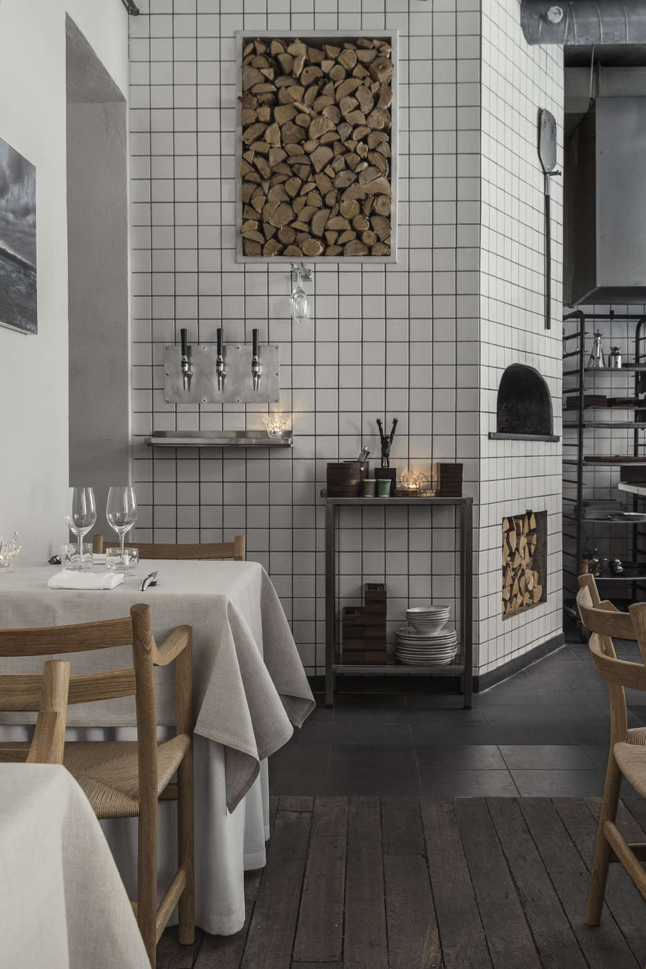 The tile continues into the dining area, where it surrounds a wood-fired oven. Niches in the wall that store cut firewood are both practical and beautiful, mixing rusticity with the glossy tile.