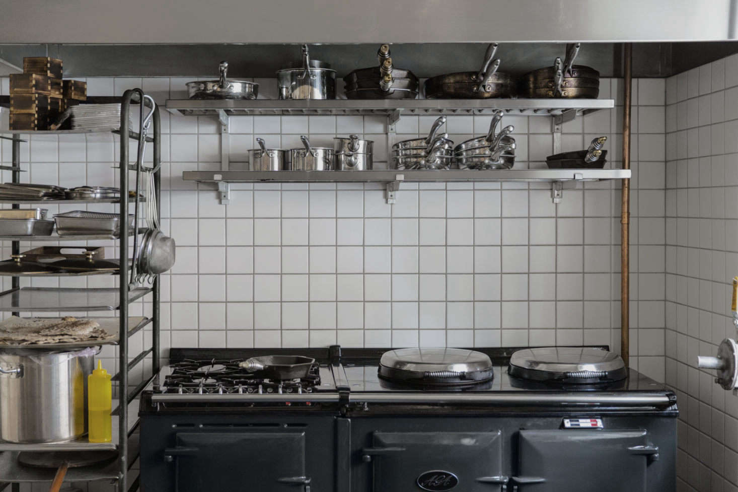 The small kitchen behind the bar (shown here when service is not in session) has simple components: floor-to-ceiling square tile, a charcoal-colored Aga range, and stacks of pots and pans.