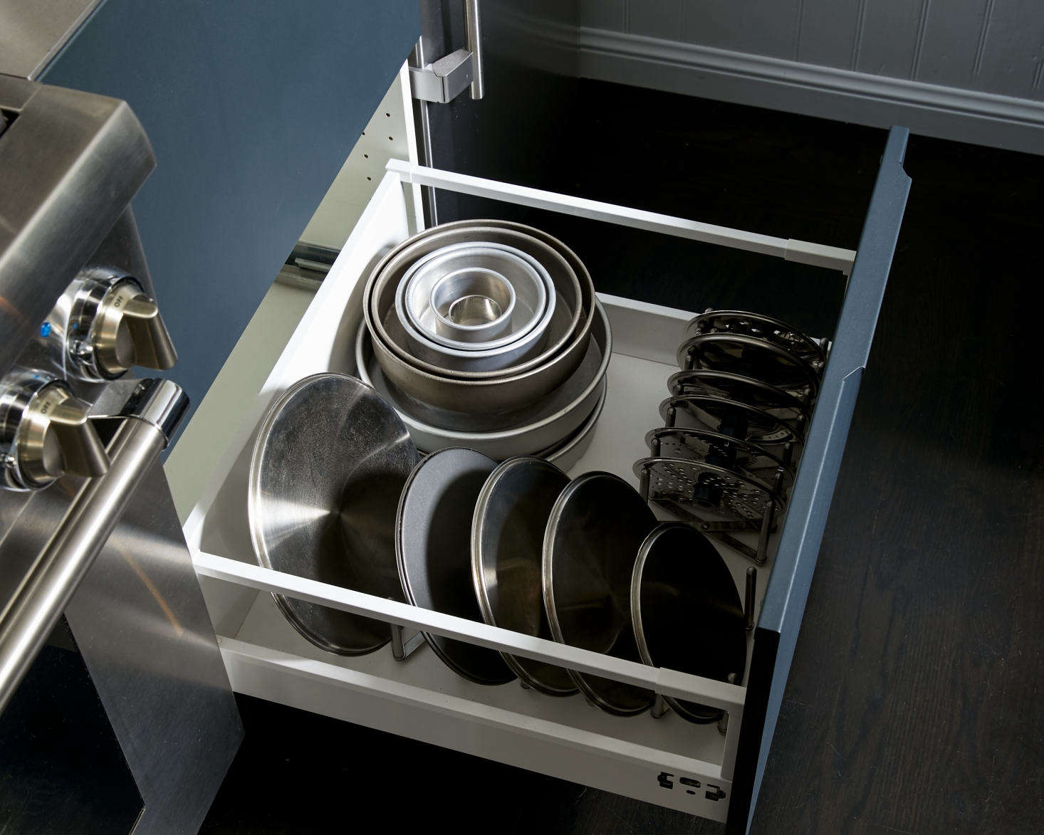 Amy keeps her pot lids neatly organized in a deep drawer to the right of the stove.
