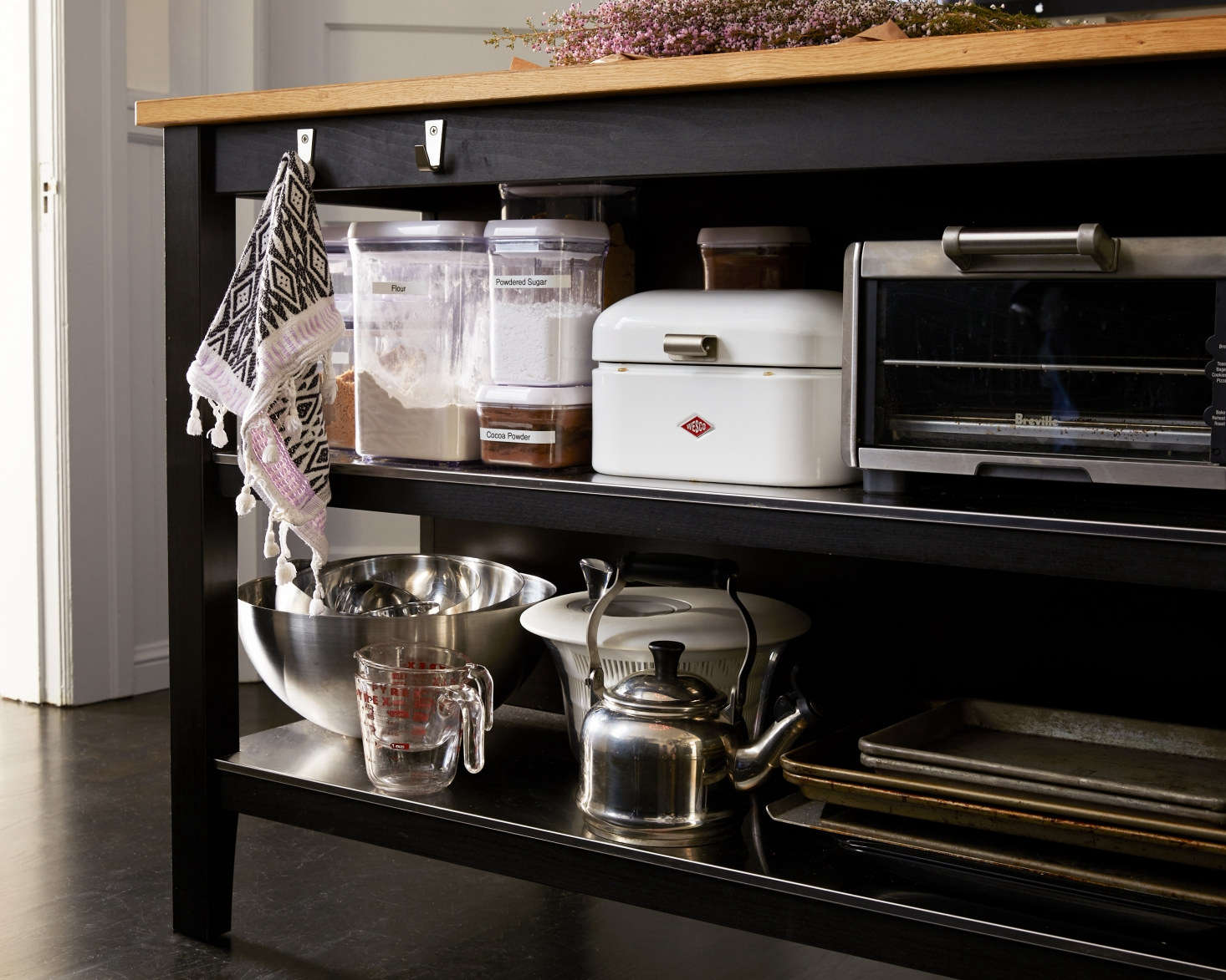 On the side of the Ikea Stenstorp Kitchen Island facing the sink, Amy stores her culinary essentials out of sight, including tea kettle, labeled baking essentials, and stacks of jelly roll pans. &#8