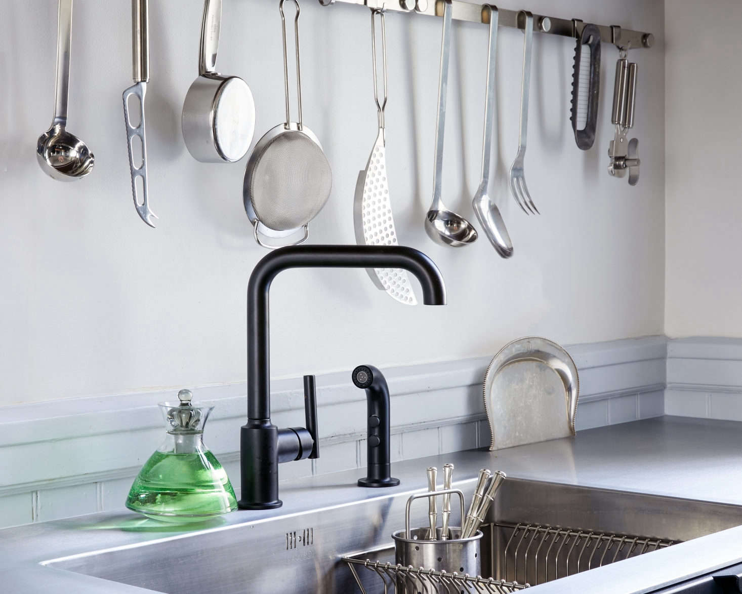 The open kitchen utensil rail is from German company Rosle and the matte black Purist Single Handle Faucet is from Kohler. &#8