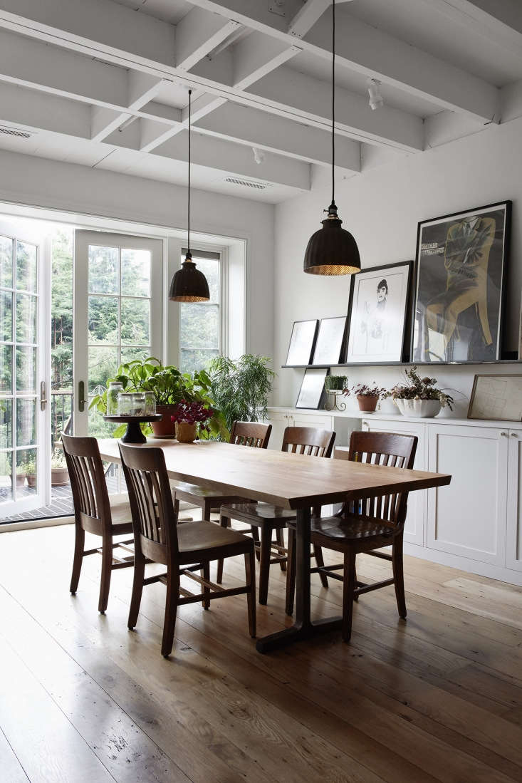 a mix of old wooden office chairs surround a mango wood table assembled at from 16