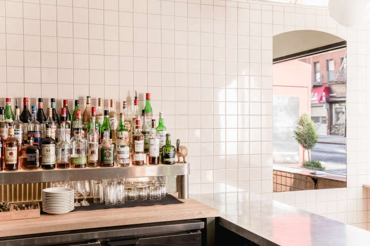 The custom, curved zinc bar is the center of the space (and all of the cooking takes place behind it). The owners also had a three-level liquor shelf custom-built by a metal shop in Williamsburg. &#8