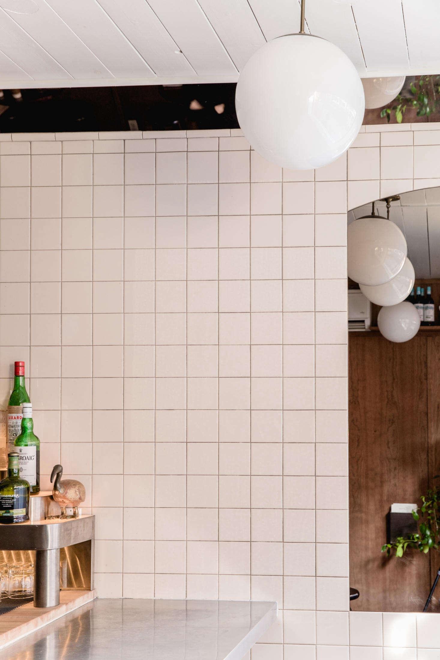 A long thin mirror runs above the bar, where the wall meets the ceiling. It&#8
