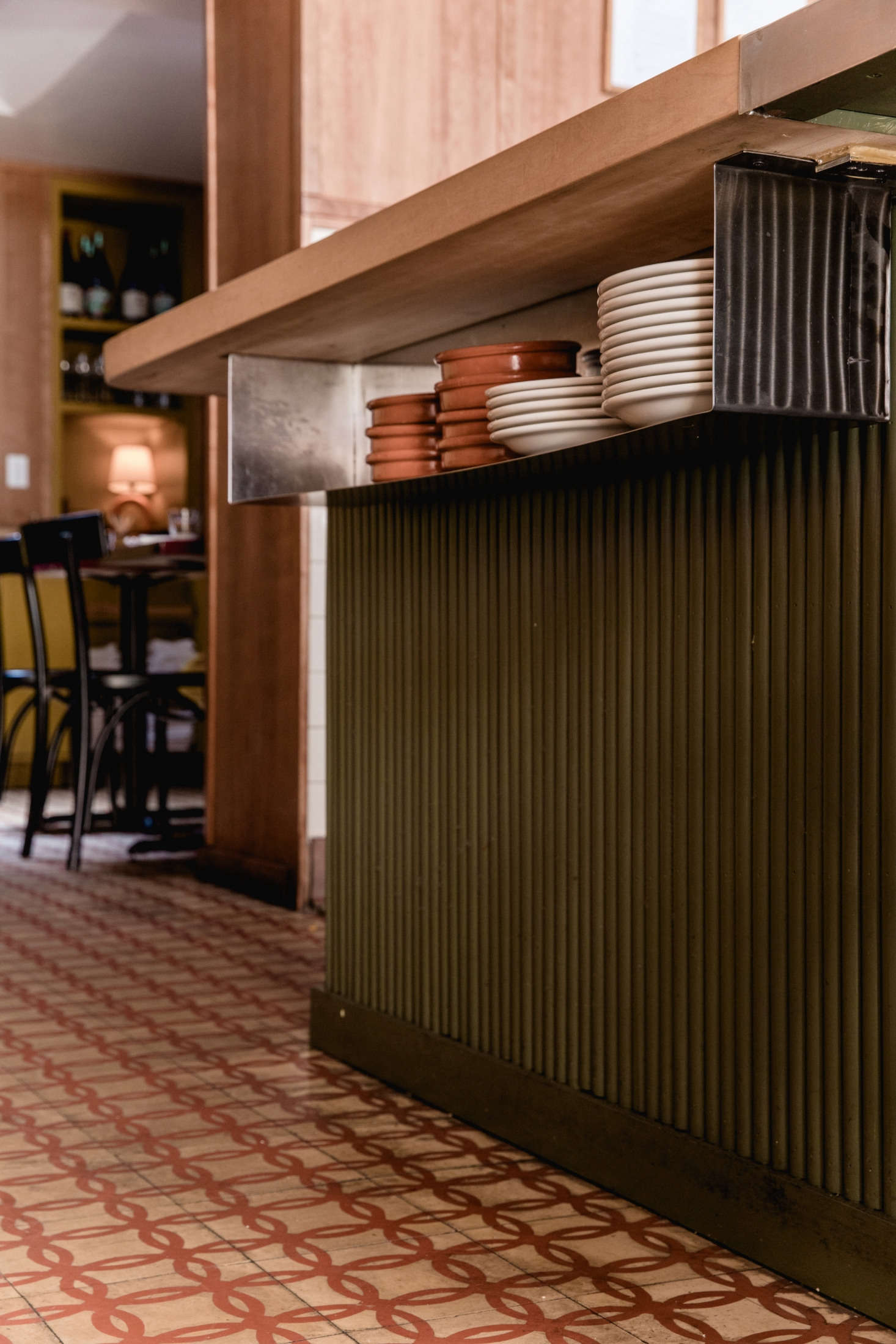 With a tight prep space, the team built storage into easy-to-access places, like this metal shelf that holds serveware underneath the bar