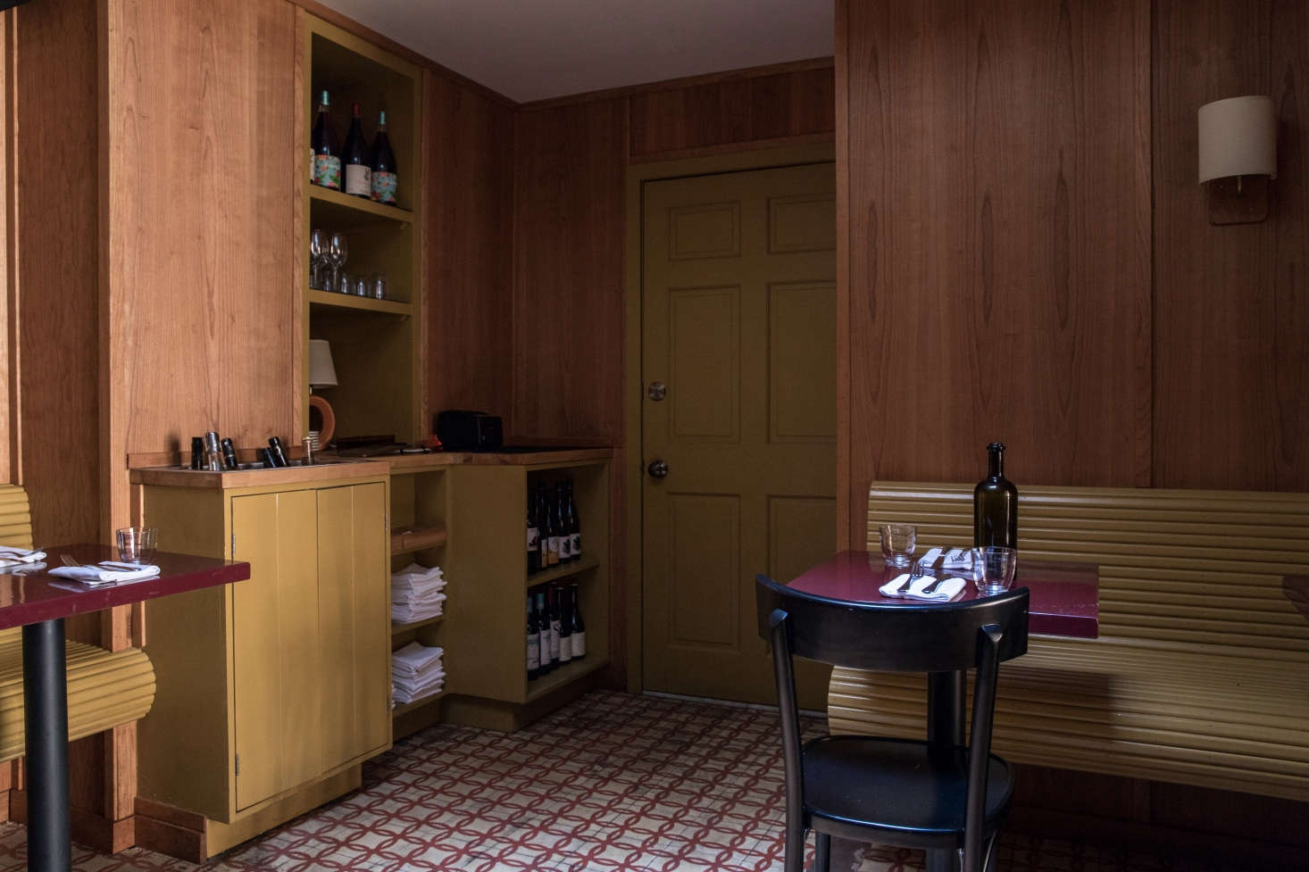 In the small back room, a wall of built-ins is both artful and efficient. The benches, cabinets and shelves, and door (which leads to the small bathroom) are all painted inBenjamin Moore&#8