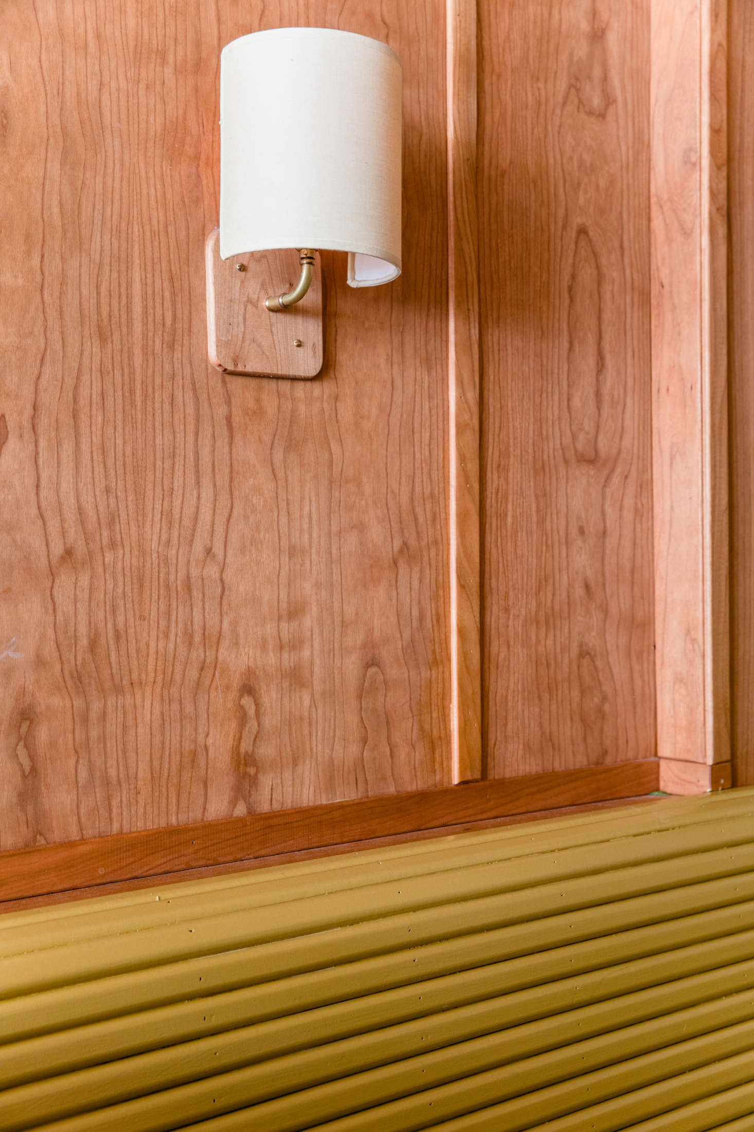 A small but impactful detail: The millwork team made small integrated panels to seamlessly fit the custom linen sconces from Broome Lampshades to the wall.