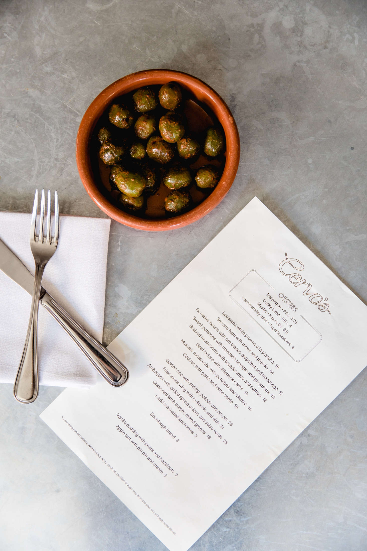 The restaurant serves small dishes—like warm olives with lemon zest—in terracotta dishes called cazuelas from Spain, imported from Despaña.