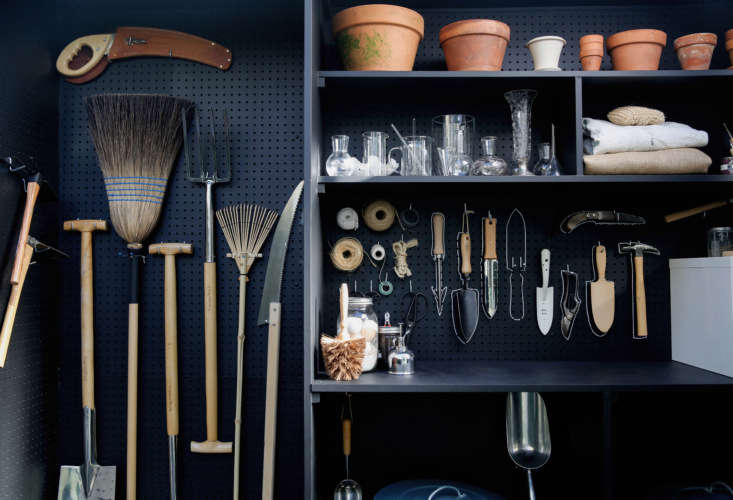long handled tools like rakes and brooms hang on one side of the shed. 16