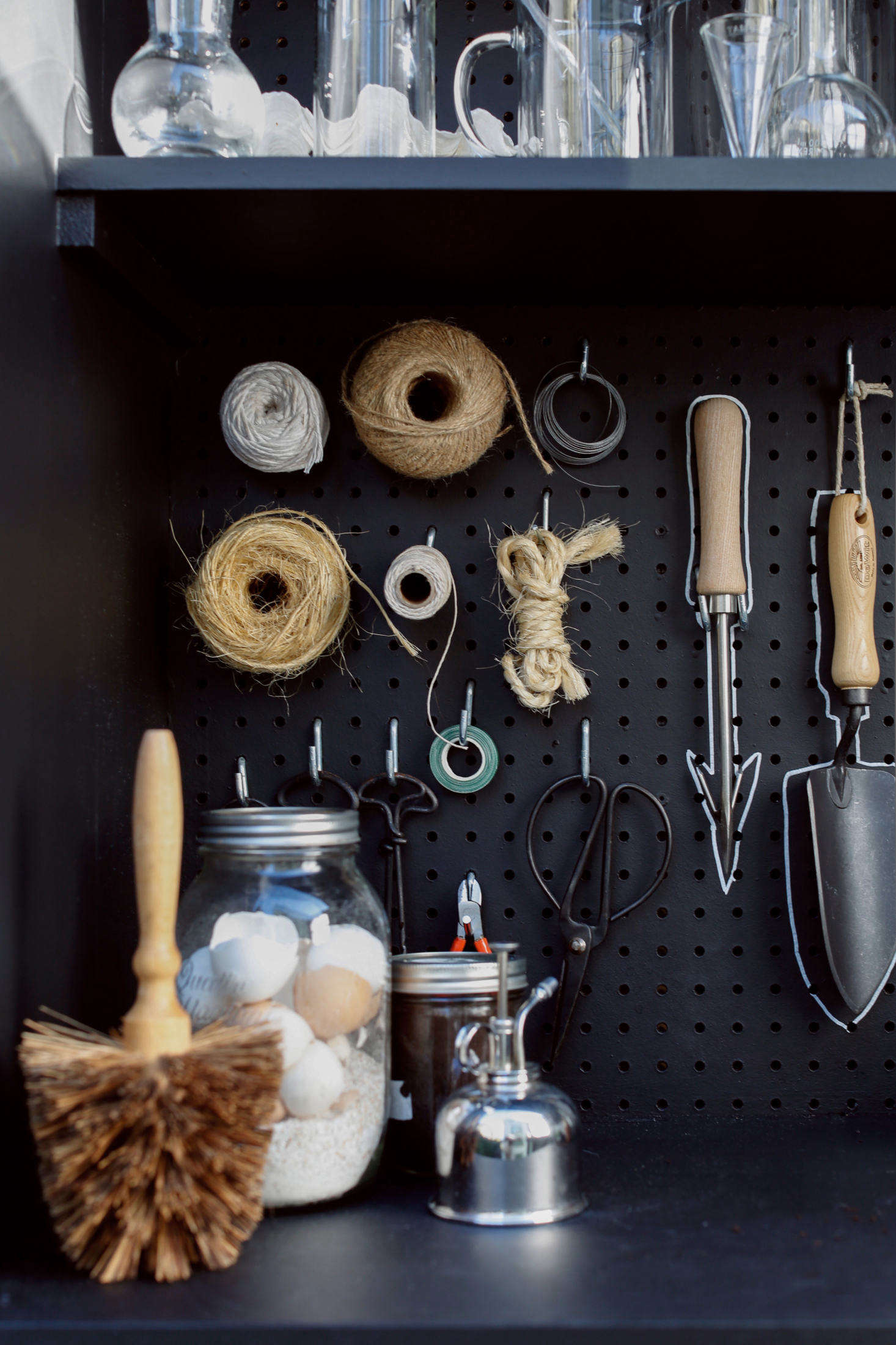 A corner of the shed holds a flowerpot brush, a plant mister, and a jar of eggshells. (Why the eggshells? See Gardening src=