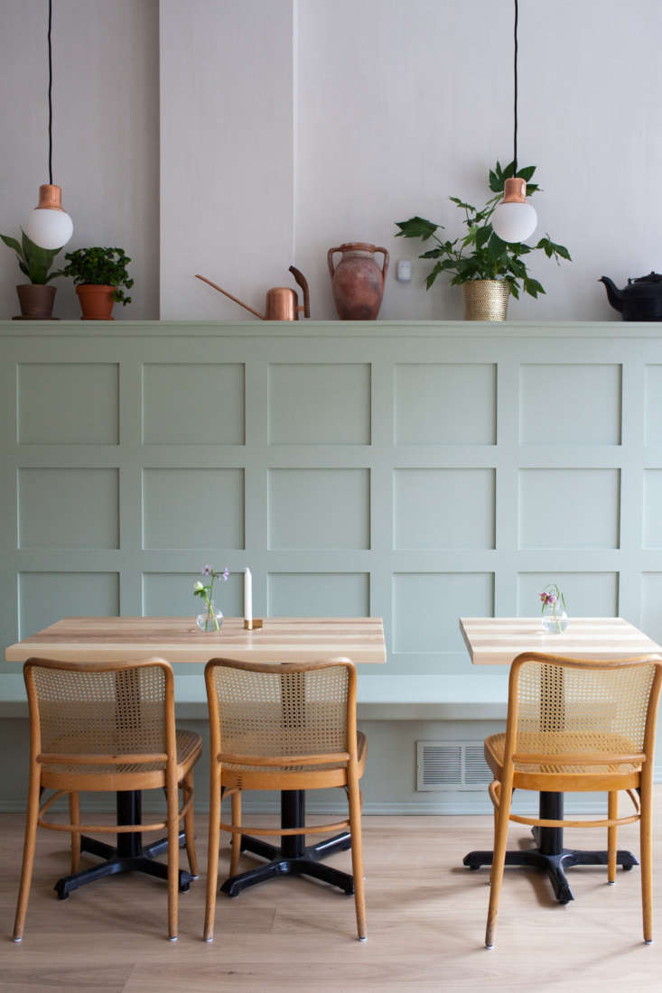 The paneling reads like a high-back bench; on the top shelf are mix-and-match antiques, &#8