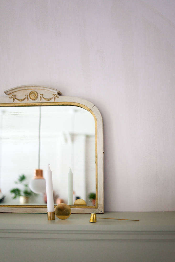 A geometricFundament Brass Candle Holder and aLong Brass Candle Snuffer (available for $80 CAD from Mjölk) mix with a vintage painted mirror on the high shelf.