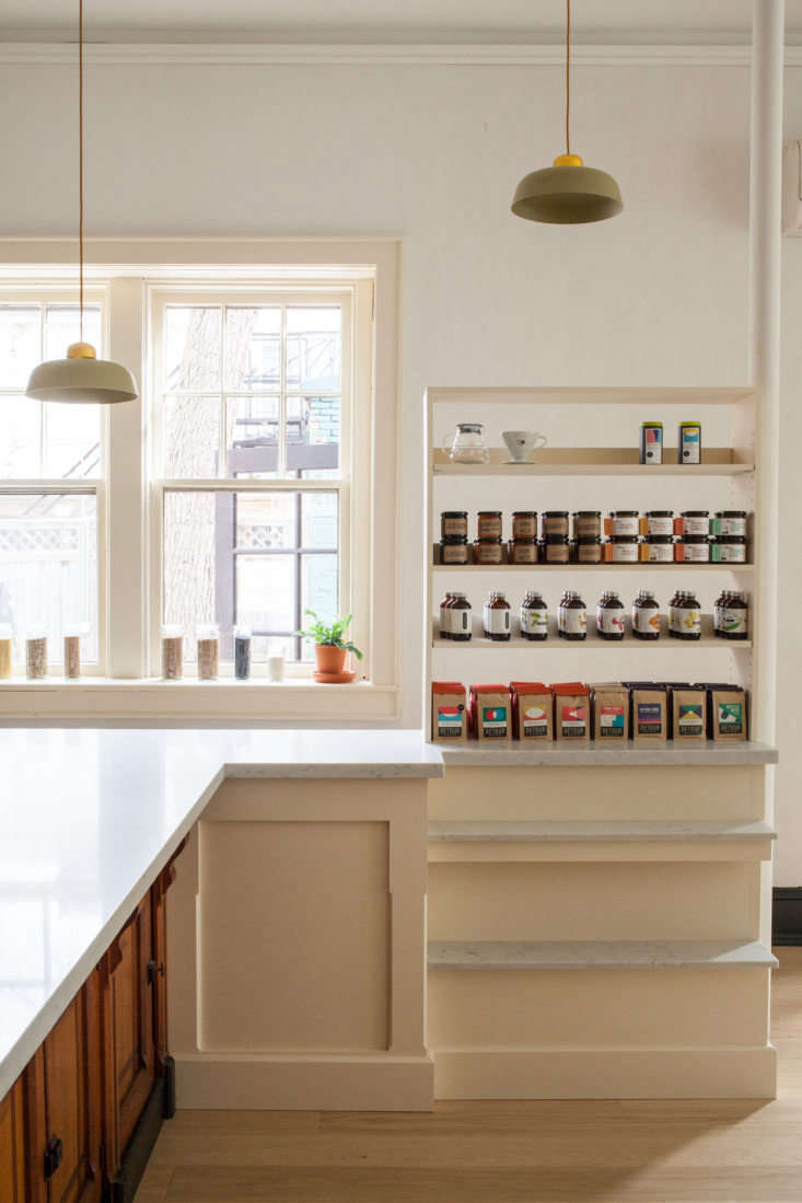 To the right of the coffee counter, custom shelves painted in Hay by Farrow & Ball topped with marble slabs stock provisions for sale.