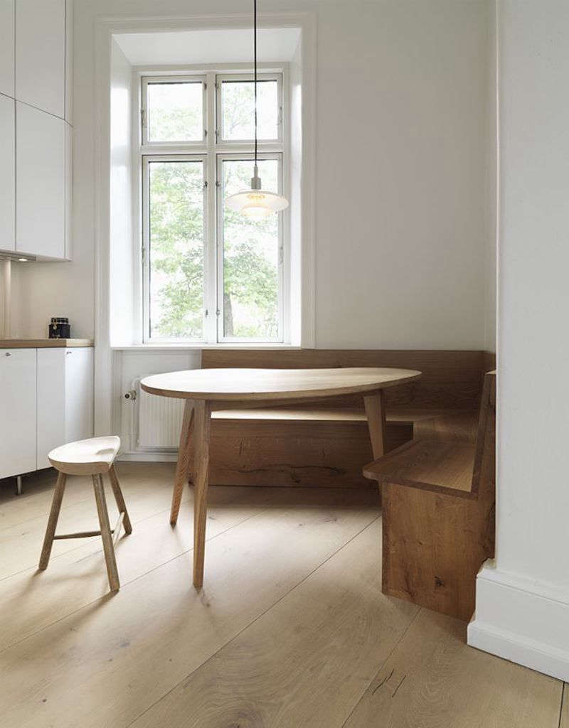 A Copenhagen kitchen features Dinesen Heart Oak furniture (and floors) for a built-in booth. See more of the kitchen in Remodeling src=