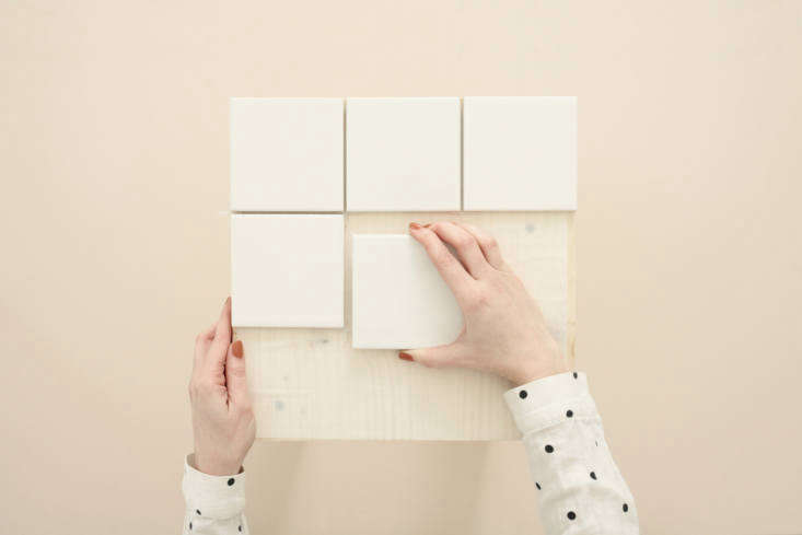 Standard 4-inch Square Ceramic Wall Tiles are $8.36 per square foot at Home Depot. Place the first one in a corner and carefully space so that the gaps between tiles are even.