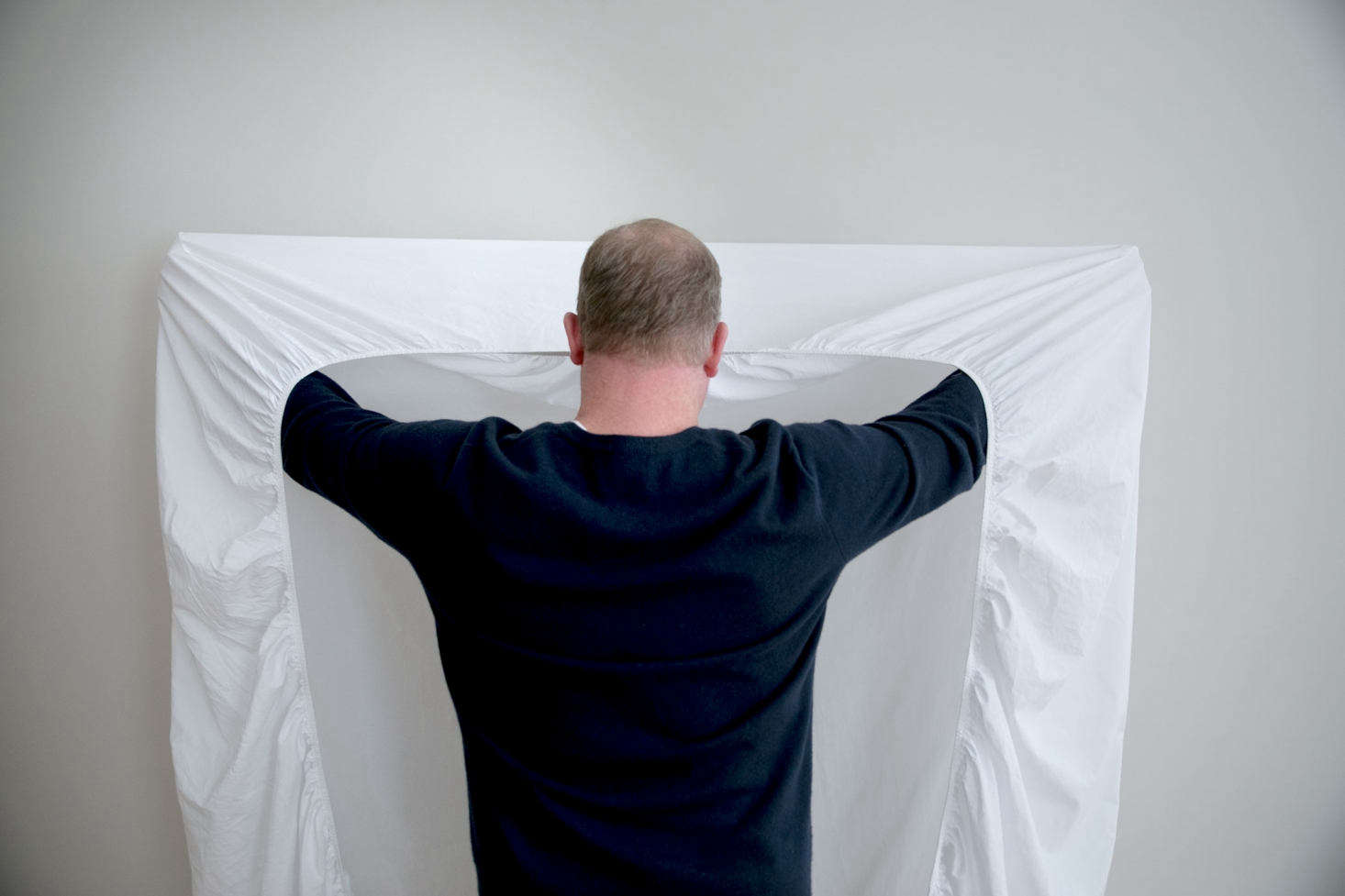 With the elastic side facing you, place your hands inside the top two corner pockets of the sheet.