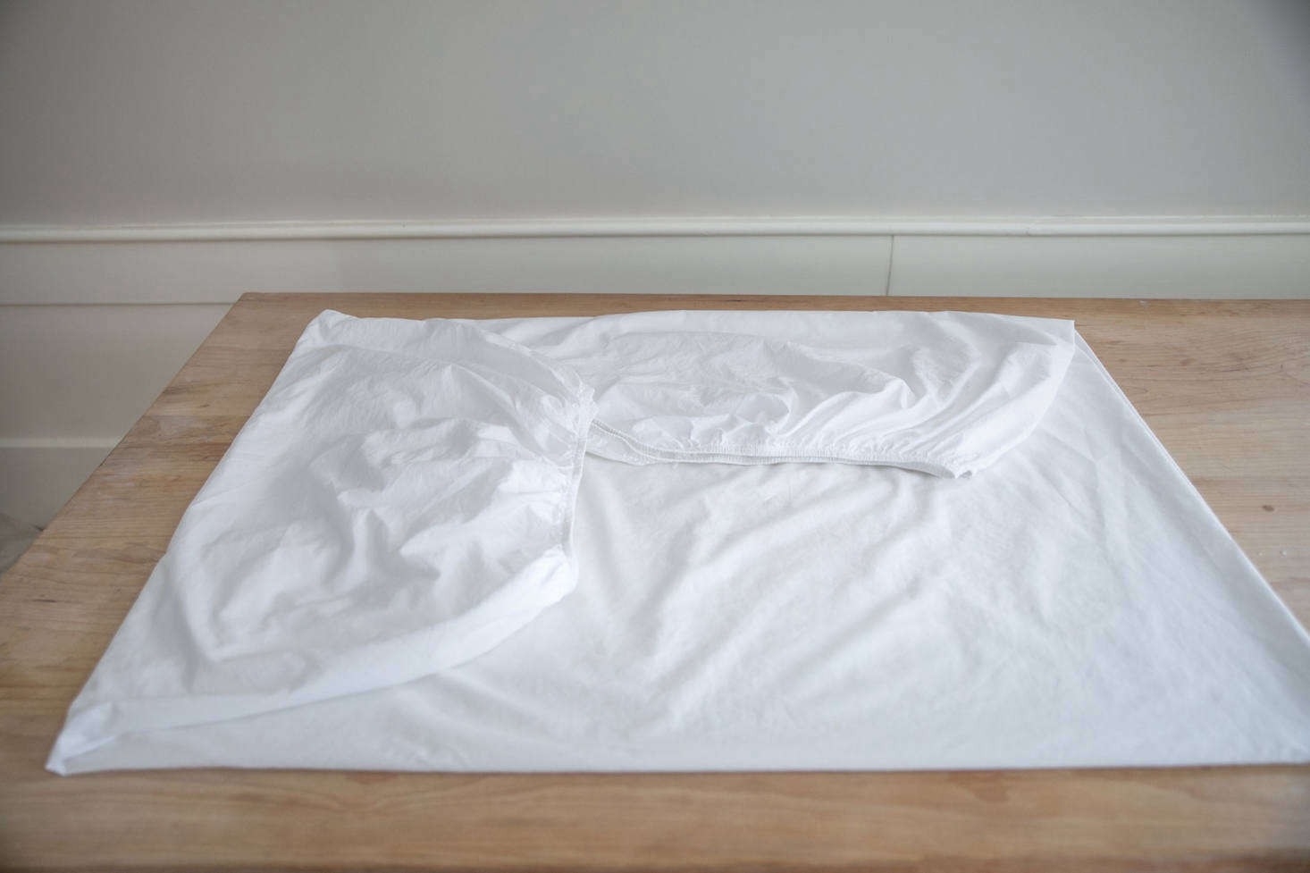Lay the sheet on a flat surface with the single corner pocket and elastic edges folded over so that the sheet is square. Smooth the sheet. Having eliminated the awkward shape caused by the elastics, you may proceed to fold your sheet as you normally would.